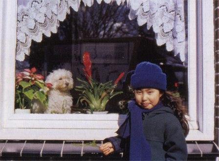 Gadis kecil di depan jendela mungil yang cantik …